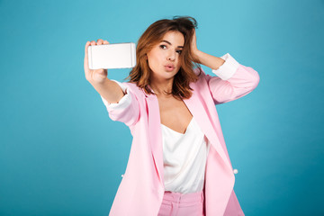 Portrait of a pretty woman dressed in pink suit posing