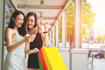 Young Beautiful Asian women in white and black dress.Holding phone, Shopping bags enjoying on street city. Shopping Concept