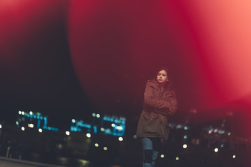 Portrait of pensive young woman walking in a promenade with city lights bokeh on backgorund