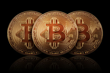 Three Gold Bitcoin on dark background. Banking business.