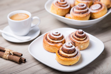 Fresh homemade buns with cinnamon, a cup of coffee, cinnamon sticks. Selective focus, close-up