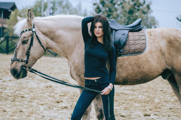 Beautiful brunette rider posing with a horse, after riding in a country ranch. Horseback riding. Lifestyle Photo. Fashion photo.