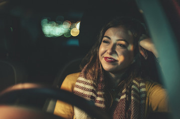 Young attractive woman looking at horizon in the car during a traffic jam with city lights bokeh on background