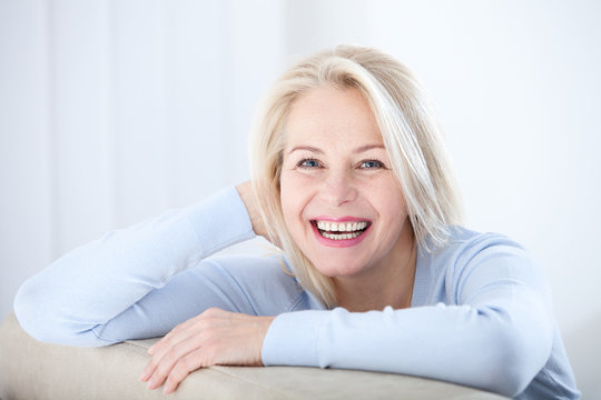 Active beautiful middle-aged woman smiling friendly and looking in camera. Woman's face closeup. Realistic images without retouching with their own imperfections. Selective focus.