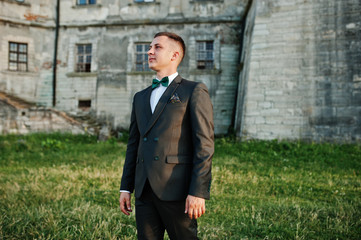 Portrait of a handsome groom standing on the grass next to the castle.