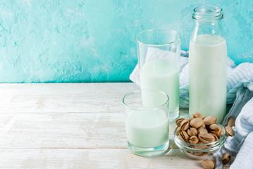 Vegan alternative food, pistachio non-dairy milk on light blue background, copy space