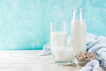 Vegan alternative food, oats non-dairy milk on light blue background, copy space