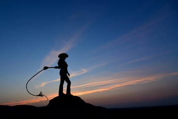 c2d37b8af53 Romantic girl in cowboy hat cracking a whip on a top rock under beautiful  colorful cloudy
