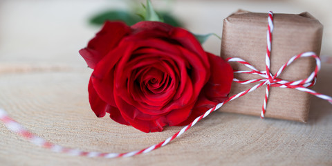 Red rose with gift on bright rustic wood