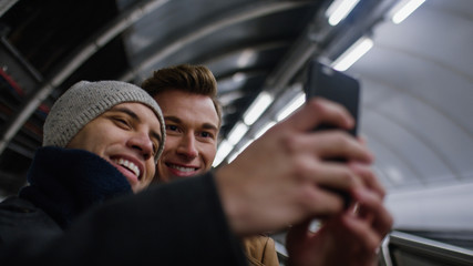 Handsome male couple take a photo together  on a subway escalator