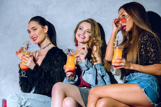attractive young fashionable multiethnic women drinking cocktails at party