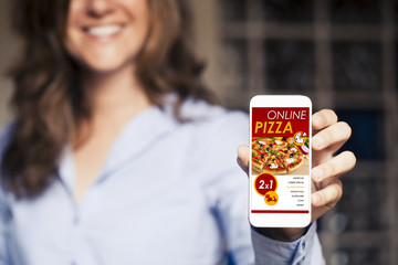 Smiling woman holding a mobile phone with pizza shopping app in the screen.