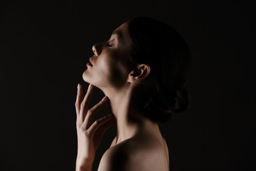 Beautiful image in profile of half-naked gentle woman posing on camera with closed eyes isolated, over black background