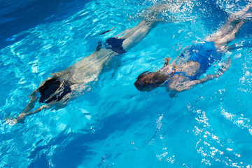Young father and child swimming in the swimming pool. View from above