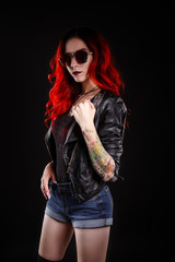 Close up of beautiful woman with tattoo wearing jeans short paint against black background.