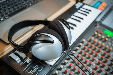 computer music, home studio equipment. headphone on midi keyboard synthesizer with laptop computer and sound mixer