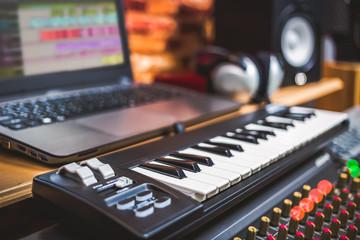 computer music, home studio equipment. midi keyboard, laptop computer, headphone and loudspeaker monitor. shallow dept of field