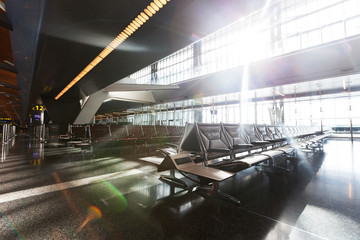 modern airport terminal with black leather seats at sunset.