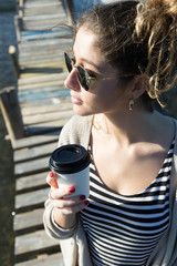 stylish young woman in wooden aged pier drinking coffee