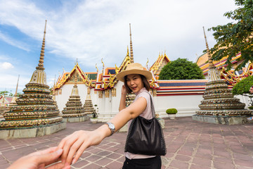Tourist women with hat sign follow me for travel in temple