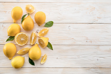 Ripe lemons and lemon leaves on wooden background. Top view. Wall mural