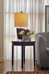 Interior shot of illuminated table lamp and colorful flowers planter on small dark brown wooden table on background of big window with white sheer curtains and grey armchair