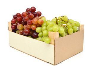 Fresh red and green grapes in a wooden crate box. Isolated on white