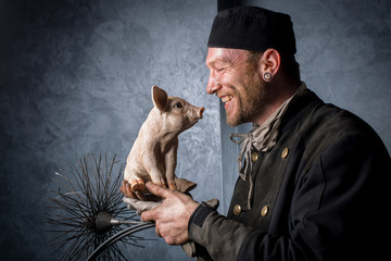 Schornsteinfeger mit Glücksschwein und Kehrbesen auf Arm vor dunklem Hintergrund