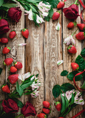 top view of strawberries and flowers on wooden shabby background, valentines background