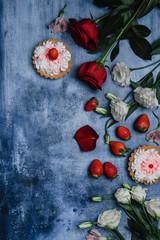 top view of strawberries, tarts and flowers on shabby background