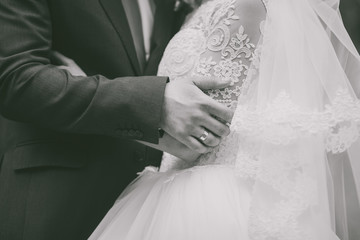 Closeup of hands of caucasian wedding couple. Black and white photography.
