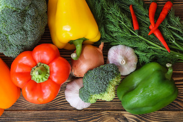 Fresh tasty vegetables. Tomatoes, sweet peppers, broccoli, garlic, dill, parsley. On a wooden background.