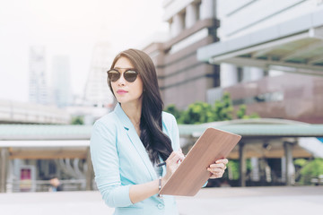 beautiful  asian business  woman holding document paperwork  on business district , business concept