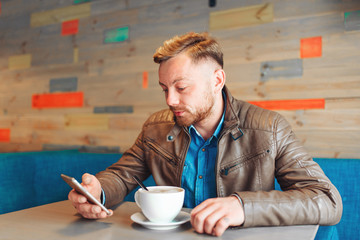 Cropped image bearded hipster guy check own mail and chatting with friends in social networks on mobile phone using free internet sitting in cafe shop with cup of coffee.Man using gadget. Guy browsing
