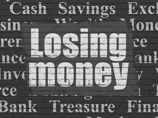 Currency concept: Painted white text Losing Money on Black Brick wall background with  Tag Cloud