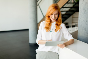 Pretty young red hair woman using digital tablet