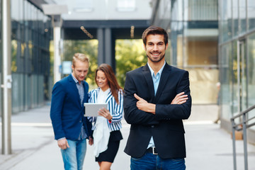Young businessman posing in front of a small group of business people