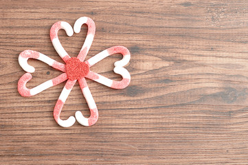 A flower pattern made out of candy canes packed in heart shapes with a small red heart in the middle