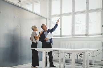 Business man and woman looking around in new office