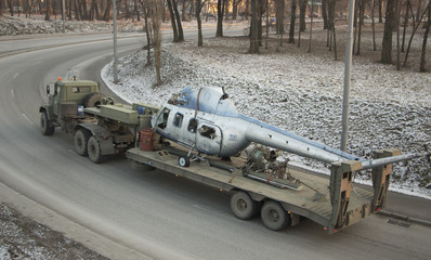 A Soviet-made military truck is transported by a broken helicopter