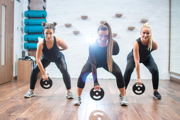 Group of three young sporty women exercising with weights at gym.