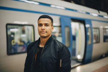 Portrait of man standing by train at subway station