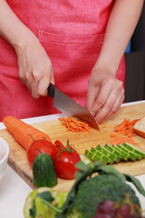 hand cutting carrot on board in kitchen room