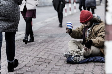 Hopeless beggar on the sidewalk