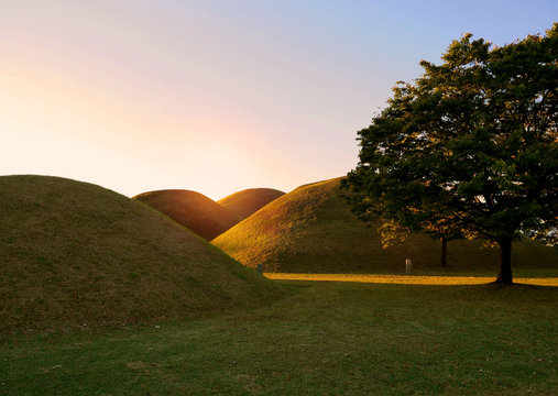 The sun rise over the Tumuli park royal tombs complex located in Gyeongju, South Korea.