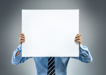 Office worker in blue shirt holding white blank. Copy space for your text. Close up. Business concept