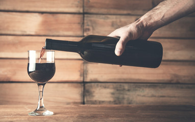 Hand pouring red wine into a glass on a wood background