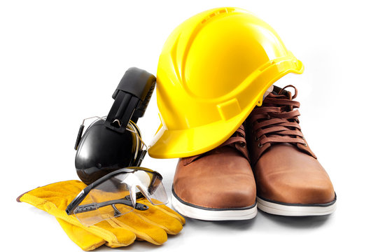 Work safety concept with hard hat, protective gloves, boots, eye safety glasses and hearing protecting noise canceling earmuffs isolated on white background with a clipping path included