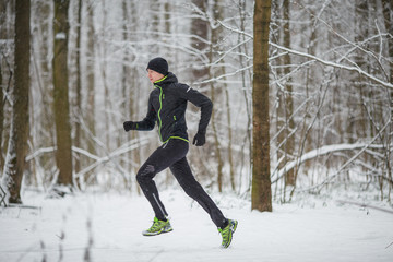 Photo from side of man in sports clothes on run in winter