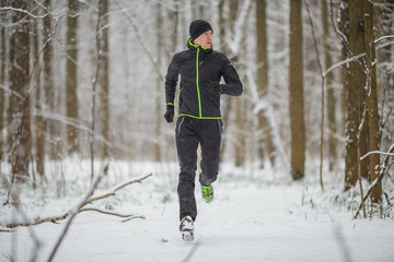 Photo of man in sportswear, black hat jogging in winter